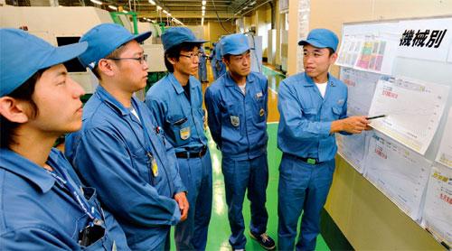 写真1●TOC推進事務局が定めた目的を現場で説明する生産管理センターの小川猛技師(写真右端)(写真撮影:福尾 行洋)