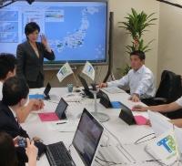 写真●チームが用いる専用の部屋で、取り組みを解説する小池百合子衆議院議員(中央左側)と平井卓也衆議院議員(中央右側)