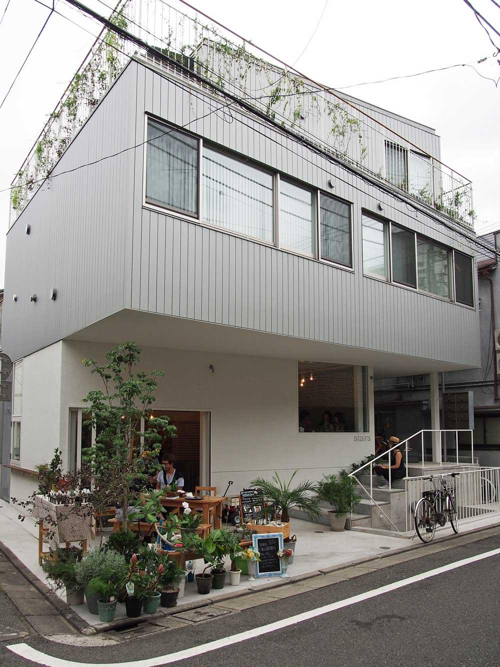 道路に面した北側外観。1階に食堂がある。3つの箱をずらして積層し、1~3階のSOHO住戸につながるテラスと階段がらせん状に外周を取り巻く(写真:飯田 彩)