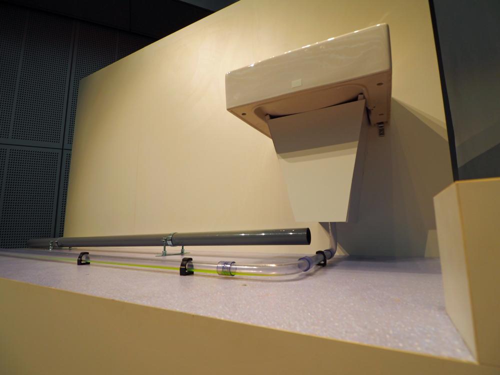 サイホン排水システムのモデル。手前の細い管がシステムを採用したもの。勾配を付けることなく設置できる。奥のグレーの塩ビ管は従来の一般的な排水管。このモデルはデモンストレーション用に用意されたもので、使用する管は中の排水の様子が見えるように透明になっている。実際の管は中が見えない状態(写真:日経アーキテクチュア)