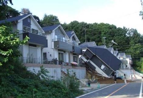 豪雨によって裏手にあった緩傾斜地で崩壊が発生。その崩土によって倒壊した住宅(写真:応用地質)